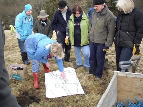 Photograph of community members looking at the orchard plan during the planting day